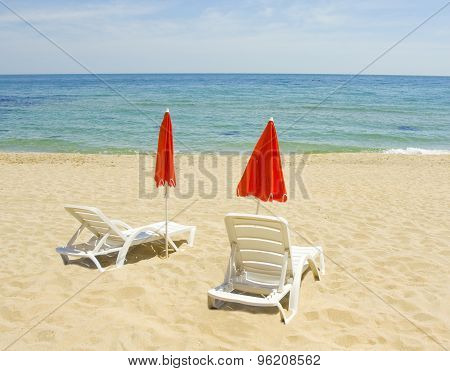 Red Beach Umbrellas And White Chaise Longues