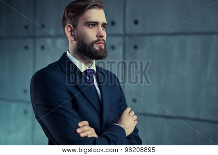 Young handsome man with beard in black suit looking aside.