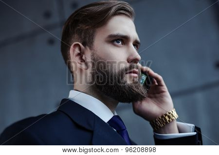Young handsome businessman with beard talking on phone portrait.
