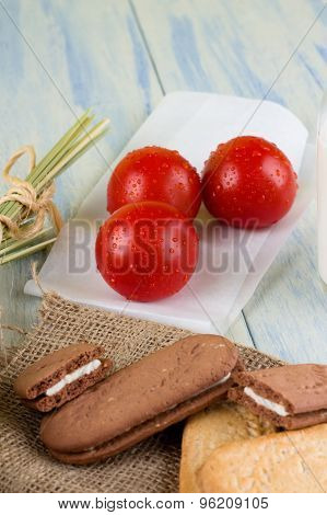 Three Dewy Tomatoes Next To Cereal Biscuits