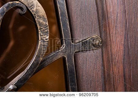 Close up fragment of metal pattern on wooden door with glass