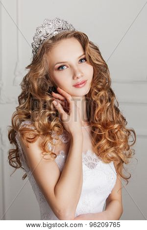 Portrait of beautiful bride with crown on white background.