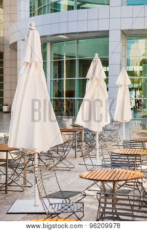 Outdoor cafe seating with round tables and white umbrellas