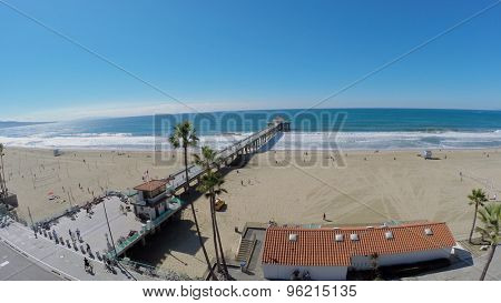 MANHATTAN BEACH - NOV 02, 2014: People walk by sandy beach and Manhattan Beach Pier at autumn sunny day. Aerial view. Pier was built in 1920.