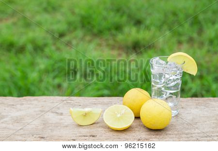 Vodka with lemon on wooden table background