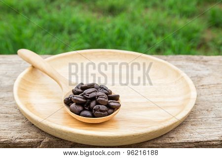Coffee Beans In Wooden Spoon On Wooden Background
