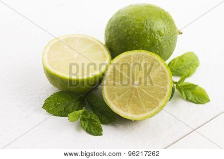 Green Limes With Mint And Water Drops On White Background