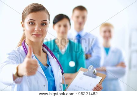Young happy female doctor showing thumbs up .