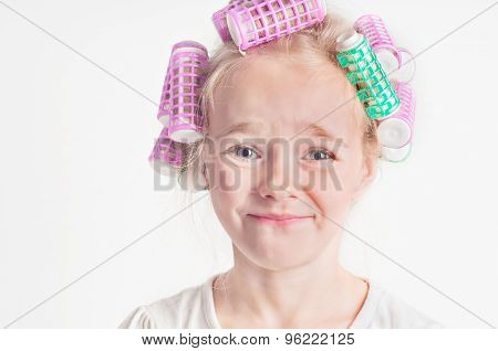Portrait of emotional cute little girl with curler