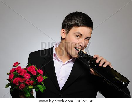 Handsome Romantic Young Man Holding Rose Flower And Vine Bottle  Prepared For A Date. Gray Backgroun