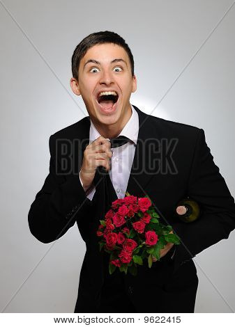 Expressions. Happy Romantic Husband Holding Rose Flower And Vine Bottle And Unknotting His Tie. Gray