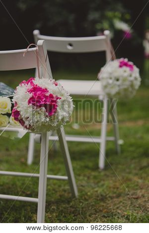 White wedding chairs with beautiful flower.