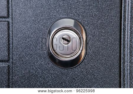 Close up of keyhole in round lock on iron, metallic background, safety concept. Door element