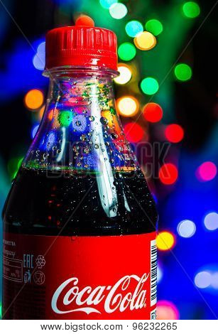 The Coca-Cola bottle on a background colorful bokeh.