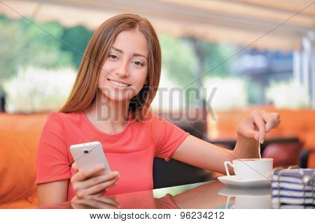 Pretty young girl in cafe with mobile phone