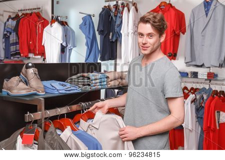 Man choosing shirt for himself in boutique
