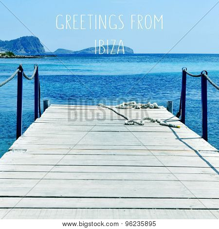 an aged wooden boardwalk over the Mediterranean sea in Ibiza Island, Spain, and the text greetings from Ibiza, with a retro effect