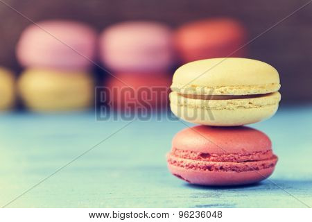 some appetizing macarons with different colors and flavors on a blue rustic wooden surface, cross processed