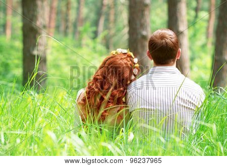 Back side of cute peaceful couple sitting on grass in the park, relaxing outdoors, enjoying romantic date