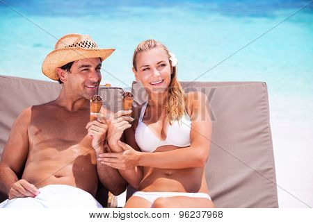 Happy couple on the beach sitting on sunbed and eating ice cream, with interest looking in side, enjoying summer vacation
