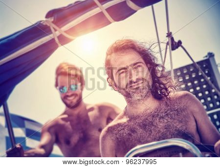 Two men on sailboat, traveling along sea, water trip in the evening in bright sunset light, summertime activity, luxury summer vacation