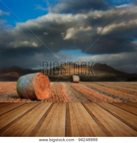 Landscape Of Hay Bales In Front Of Mountain Range With Dramatic Sky With Wooden Planks Floor