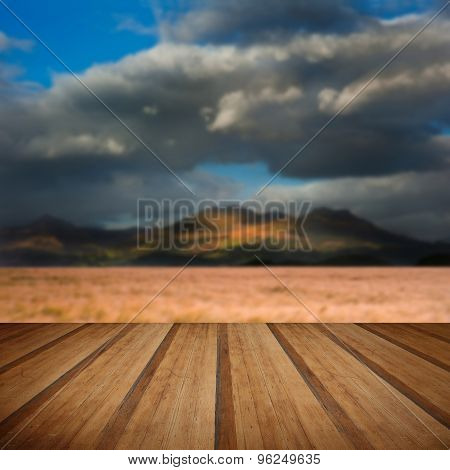 Landscape Of Windy Wheat Field In Front Of Mountain Range With Dramatic Sky With Wooden Planks Floor