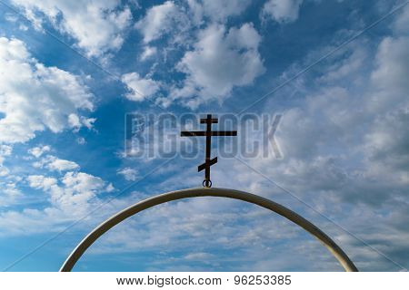 White Semi-circular Arch Of Iron Pipe With Dark Orthodox Cross On It Against The Blue Sky With Cloud