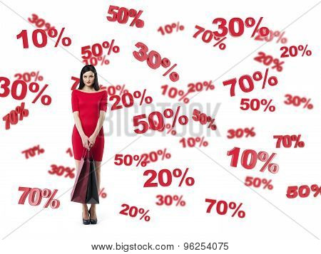 Happy Brunette In A Red Dress With The Shopping Bags. Discount And Sale Symbols: 10% 20% 30% 50% 70%
