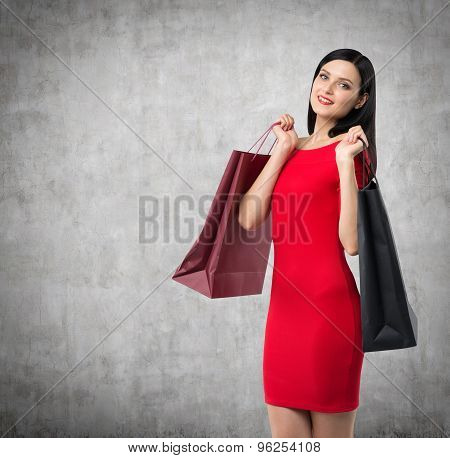 Beautiful Brunette Woman In A Red Dress Is Holding Fancy Shopping Bags. Concrete Background.