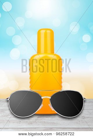 sun lotion with sunglasses and a beach background
