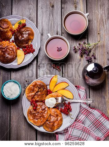 Cheesecakes With Fruits And Berries And Two Cups Of Tea On  Wooden Table.