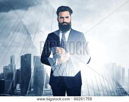 Double exposure of young bearded businessman and city on the background