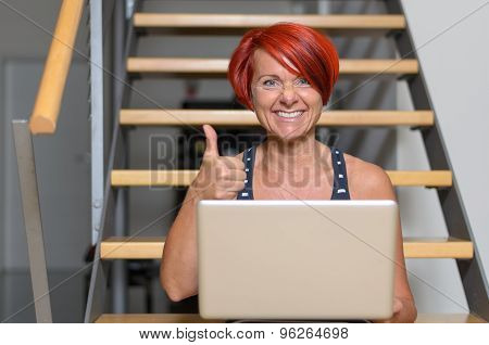 Middle Aged Woman With Laptop Showing Thumbs Up