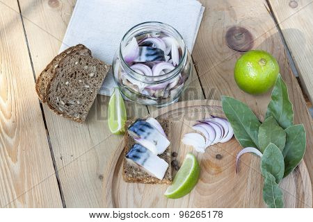 Slices of marinated mackerel with onion in a jar, lime, laurel and bread