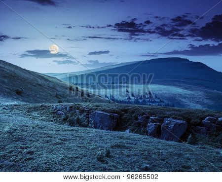 Mountain Peak Behind Hillside With Boulders At Night