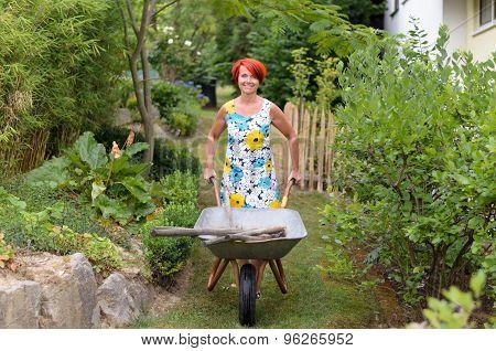Happy Woman Pushing A Wheelbarrow With Tools