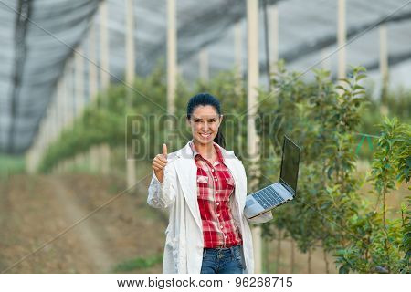 Satisfied Woman Agronomist In Orchard