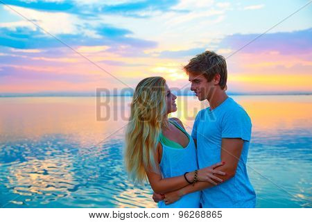 Blond young couple hug in sunset sea lake happy together