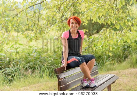 Woman Sits On The Back Of Bench Against Greenery