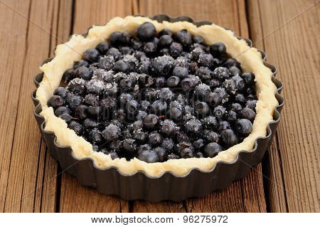 Raw Homemade Round Tart With Whole Wild Blueberries In Metal Baking Tray On Wooden Table