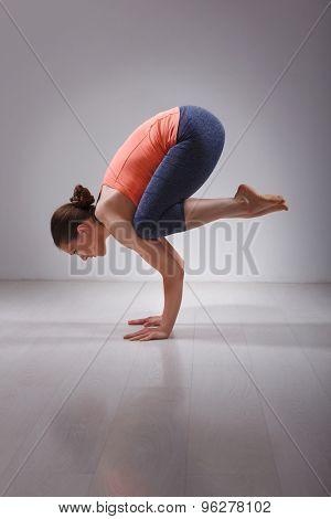 Beautiful sporty fit yogini woman practices yoga asana Bakasana - crane pose arm balance in studio