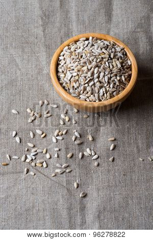 Raw peeled sunflower seeds in wooden bowl over linen napkin