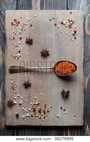 Spice Saffron in old metal spoon over wooden background.