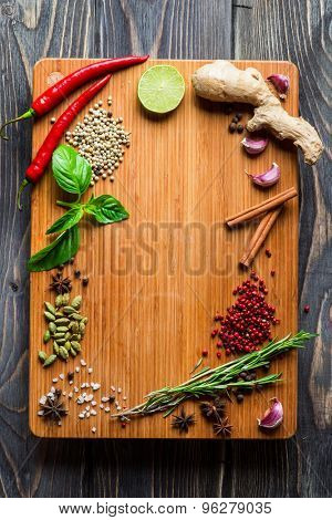 Spices over wooden background with empty place for text. Chilli pepper, cardamom, pepper corns, rosemary and sea salt.