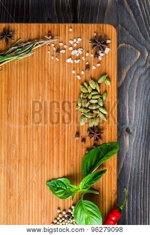 Spices over wooden background with empty place for text. Cardamon, pepper corns, anise, basil.