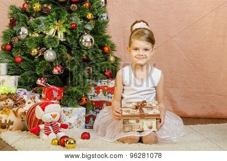 Five-year Girl With Christmas Present Sitting At Christmas Tree