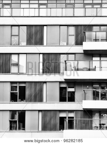 Abstract detail of the exterior of a city building, showing wood panels, windows and balconies. Black and white.