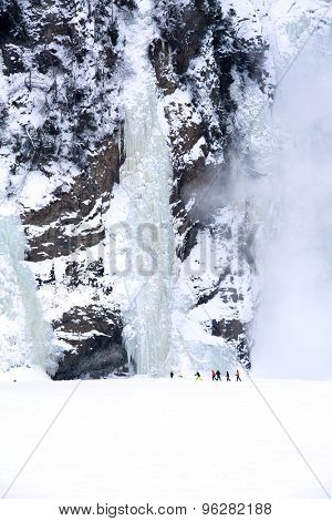 Walkers are dwarfed by the frozen Montmorency Falls, Quebec City, Canada