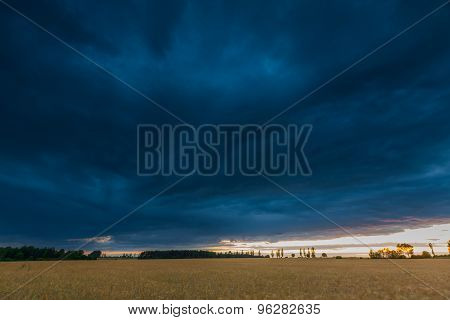 Landscape With Dark Stormy Sky Over Fields At Twilight